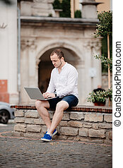 Man working on laptop at the wooden bench outdoors -...