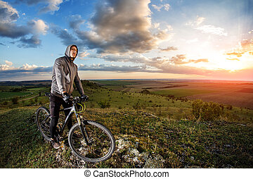 Young man cycling on a rural road through meadow - Young man...