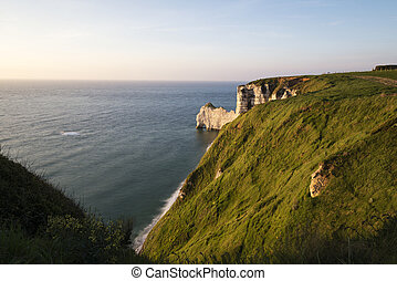 Scenic view of Etretat with its beach and famous cliffs with arches at sunset.