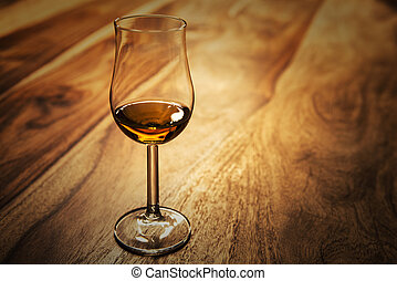 Nosing glass with scotch single malt whisky on the old...