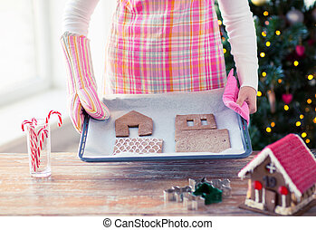 closeup of woman with gingerbread house on pan - holidays,...