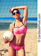 young woman with volleyball ball and net on beach - summer...