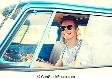 smiling young hippie man driving minivan car - summer...
