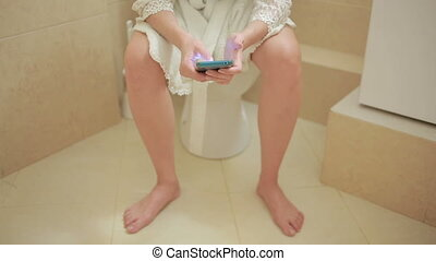 woman sitting on toilet in the bathroom. using smartphone. home bathrobe