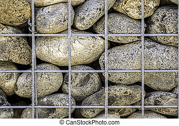 Caged stones abstract pattern - Large rocks supported by a...