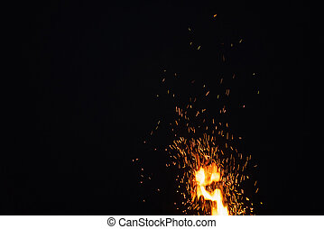 sparks from bonfire in the night with dark background,...