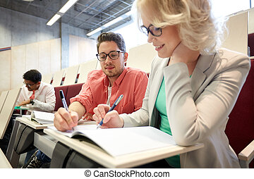 group of students with notebooks at lecture hall -...