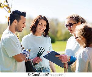 group of volunteers planting trees in park - volunteering,...