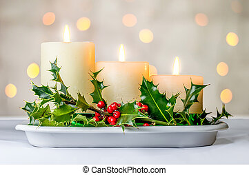 Christmas candles and holly berries with bokeh.