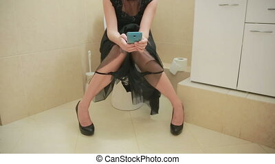woman sitting on toilet in the bathroom. using smartphone....