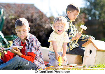 Happy kids brothers making wooden birdhouse by hands - Happy...