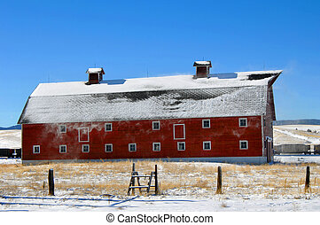 Barn and Blowing Snow - Snow blows from the rood of a red,...