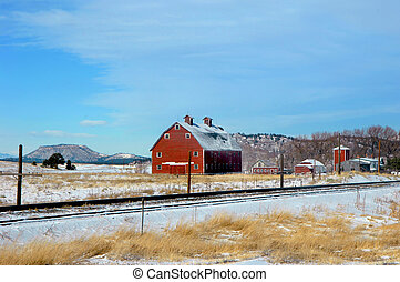 Big Red Barn - Snow lays around railroad tracks and sits on...