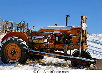 Cold Weather Covers Tractor - Orange tractor sits outdoors...