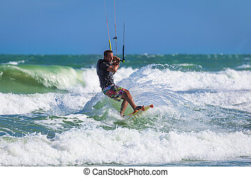 Athletic man riding on kite surf board in sea waves -...