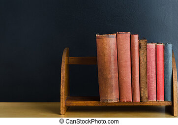 Bookshelf on Desk with Chalkboard Background - A row of old...