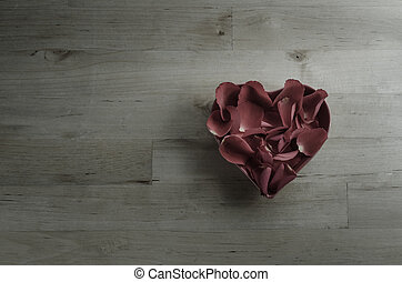 Overhead of Rose Petals Filling Heart Shaped Bowl - Rose...