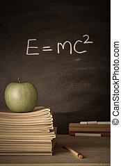 Teacher's Desk with Books, Apple and Theory on Chalkboard -...