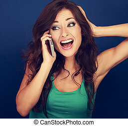 Beautiful emotional woman talking on mobile phone and loud...