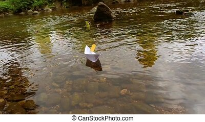 Change of seasons. Origami paper boat sailing from summer to...