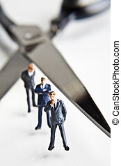 Businessman figurines standing next - Cutting back the work...