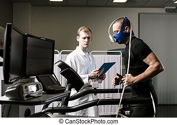 Performing a treadmill test - Shot of a male patient running...