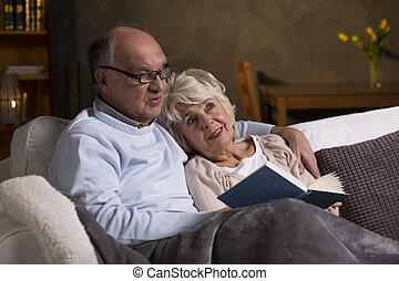Senior citizens on the couch - Two retired people relaxing...