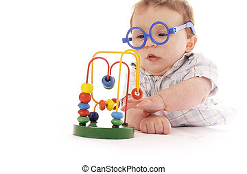 Infant baby on a white background in glasses with a toy
