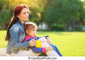 Mother with daughter outdoors - Beautiful calm female with...