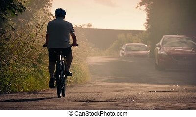 Cyclists Passing In Evening Haze - Man and woman cycling...
