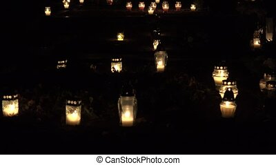 candles flame light on grave on All saints day in cemetery...
