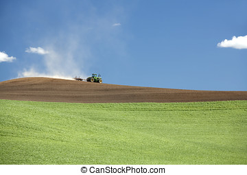 Tractor in the field - A tractor moves its way across a...