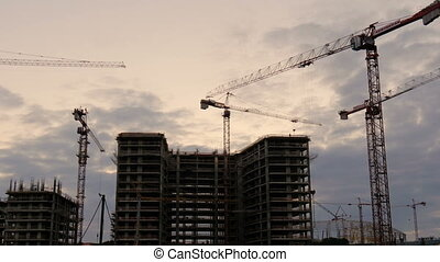 Crane working in big construction site in evening time