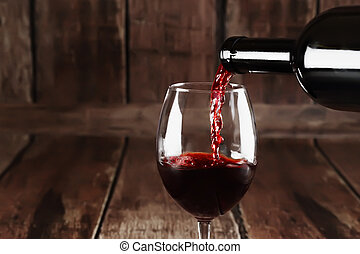Red wine is poured from bottle to glass