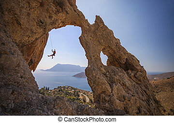 Rock climber hanging on rope while climbing cliff