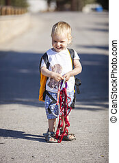 Little boy holding rock climbing gears and smiling