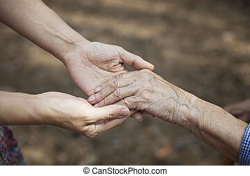 Young woman holding hand of senior