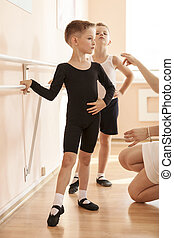 Young boys working at the barre in a ballet dance class....