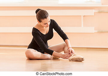Young ballet dancer putting on pointe shoes while sitting on...