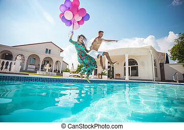 Happy young couple jumping into the pool while holding a...