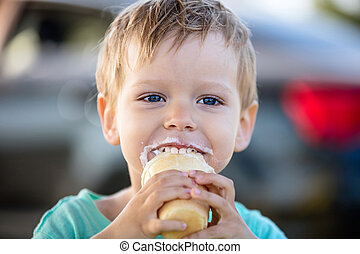 Cute little boy eating ice-cream and smiling