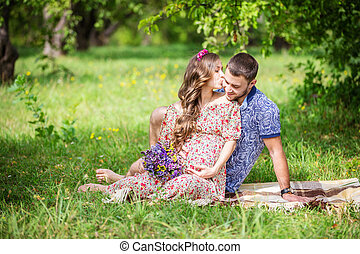 Happy young couple expecting baby, pregnant woman kissing...