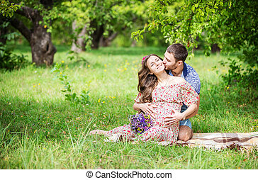 Happy young couple expecting baby, guy kissing his pregnant...