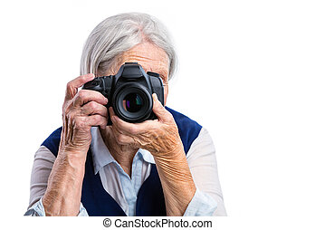 Senior woman shooting with a digital camera over white...