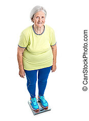 Senior woman weighing herself on scales over white...