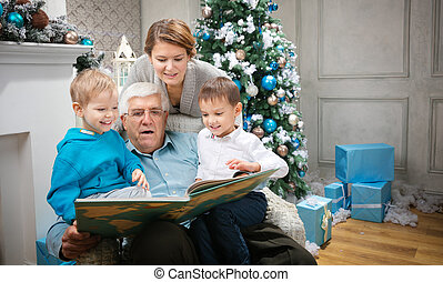 Three generation family reading a book at Christmas Eve at...