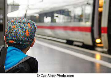 boy with a cap waits for train on railway platform - the...