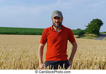 bearded man standing in a wheat field on  sunny day