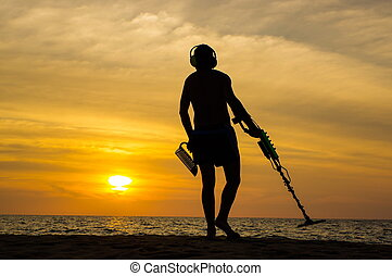 Treasure hunter with Metal detector on the sunset the beach...