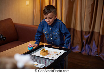 Birthday boy blowing out the candles on his cake. - Kid...